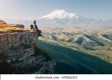 Traveler sitting on top of Bermamyt plateau and looking on Elbrus mountain. Karachay-Cherkessia, Caucasus, Russia.