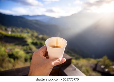 Traveler sitting on top of rock over the summer forest and pouring Coffee from thermos to cup. Point of view shot