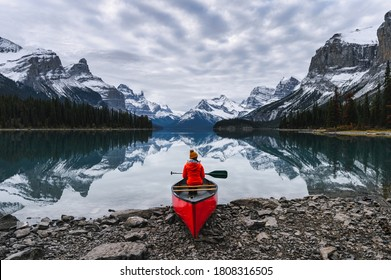 Traveler sitting with paddle on canoe in Maligne lake at Spirit Island, Jasper national park, Canada