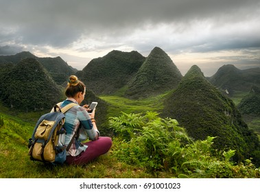 A traveler with a smartphone is exploring a picturesque karst mountain plateau in the North of Vietnam.