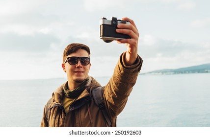Traveler smiling young man takes photographs self portrait with old photo camera on coastline on background of sea. Focus on man