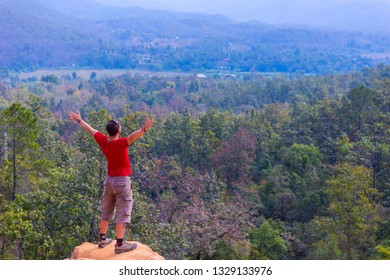 Traveler spreads hands expressing happiness with beautiful green valley on the background. Pai, North of Thailand.