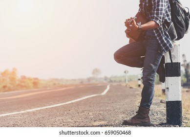 Traveler standing at the highway hitching. Man holding Guitar with Backpacks  in casual Travel Clothes walking along road ,Road hitch-hiking.