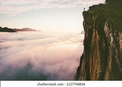 Traveler standing on cliff edge mountain top above sunset clouds travel adventure lifestyle summer journey vacations