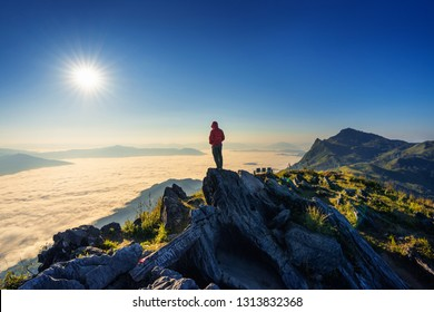 Traveler standing on the rock. Doi pha tang mountains and morning fog in Chiang rai, Thailand.