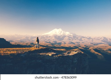 Traveler standing on top of Bermamyt plateau and looking on Elbrus mountain. Karachay-Cherkessia, Caucasus, Russia.
