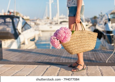 Traveler is standing in yachts port near sea with straw bag and pink  flowers hydrangea. 49ba97ba3b4cc