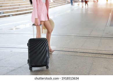 Traveler suitcase, Young asian business woman or traveler in pink casual dress carrying a black suitcase walking in a travel location on holidays trip