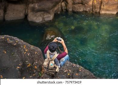 Traveler take photo on Cliff edge of stream water, Asian man traveler adventure style on the Cliff edge.