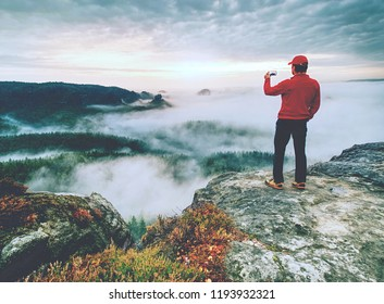 Traveler taking vacation photos of beautiful sunset in autumn nature  by smartphone, holiday or vacation travel concepts
