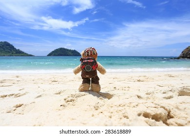 traveler teddy bear standing on sand beach , background mountain and blue sky by the sea