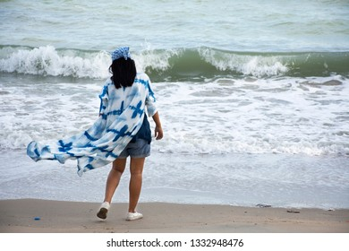 Traveler thai women wearing indigo clothes playing and relax lonely on the beach with wind and wave at Ban Pae beach in Rayong, Thailand