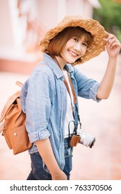 Traveler and tourist asian young women wearing backpack holding camera take a photo, travel concept, backpacker concept.