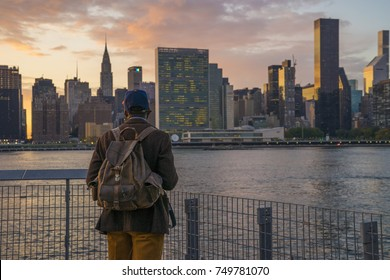 Traveler Tourist Enjoys Sunset on the Water with City Skyline