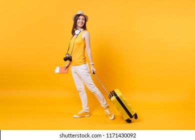 Traveler tourist woman in summer casual clothes, hat with headphones on neck isolated on yellow orange background. Passenger traveling abroad to travel on weekends getaway. Air flight journey concept