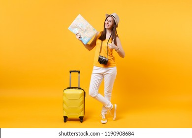 Traveler tourist woman in summer casual clothes, hat with suitcase, city map isolated on yellow orange background. Passenger traveling abroad to travel on weekends getaway. Air flight journey concept