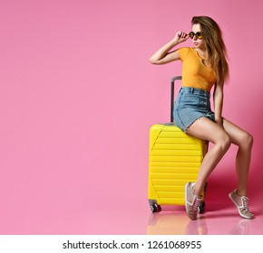 Traveler tourist woman in summer casual clothes with travel suitcase isolated on pink background. Girl sits on a suitcase and looks away. lifting glasses. Copy space
