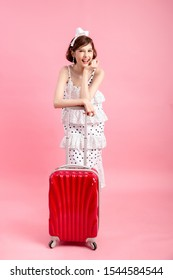 Traveler tourist woman in summer casual clothes with travel suitcase isolated on pink background