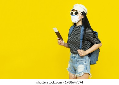 Traveler tourist young beautiful asian woman in hat and sunglasses with backpack,wearing medical face mask holding passport on yellow background.Summer holidays, vacation and travel concept