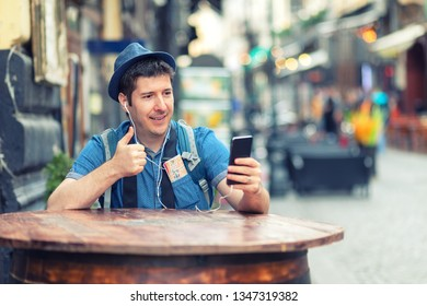 Traveler with trendy look having video call showing thumb up while exploring streets of big cities - Young man vlogging while enjoy city vibes – tourist sharing experience with friends on social media