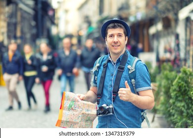 Traveler with trendy look holding map showing thumb up on street full of restaurants and shops of european city – Young man enjoying city vibes taking pictures – casual tourist exploring world alone