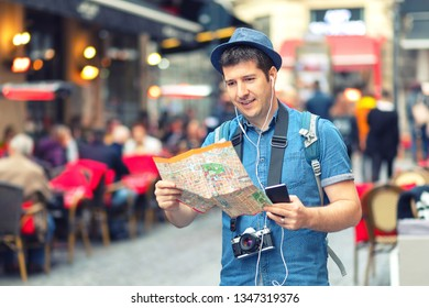 Traveler with trendy look using map on street full of restaurants and shops of european city – Young man tourist sightseeing city taking pictures with photo camera – tourist exploring world alone