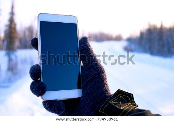 Reisende die Benutzung des Telefons im Winterwald