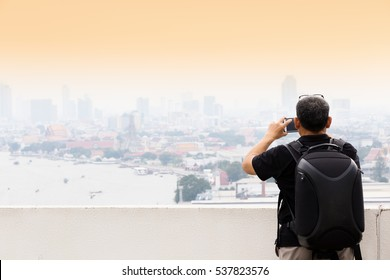 Traveler using cell phone to take photo of bangkok city
