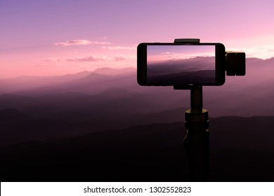 Traveler using smartphone on tripod taking a photo in sunset at the mountains natural background.