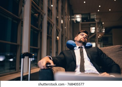 Traveler waiting at airport after flights delays and cancellations. Businessman asleep in airport lounge.