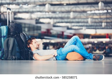 Traveler waiting at the airport departure area for his delay flight.
