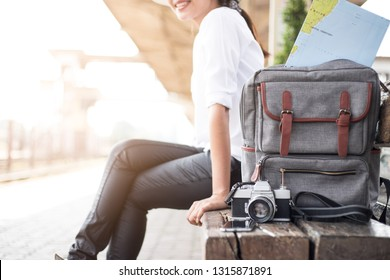 Traveler is waiting for the train to have a camera bag, map, and hat. The young woman is ready to leave for a vacation.