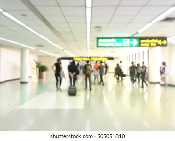 Traveler walking the airport terminal hall and a handbag behind her. Blurred background.