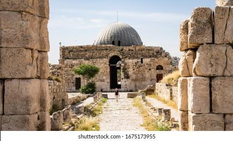 Traveler walking along Colonnated Street toward the Monumental Gateway at Umayyad Palace, Amman Citadel, Amman, Jordan, Travel concept