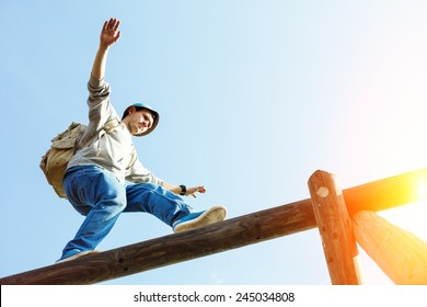 traveler walking balance over top of wooden construction