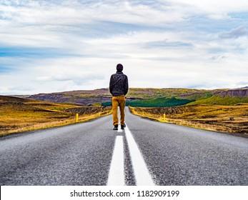 Traveler walking into the horizon on the Ring Road of Iceland enjoying the scenery