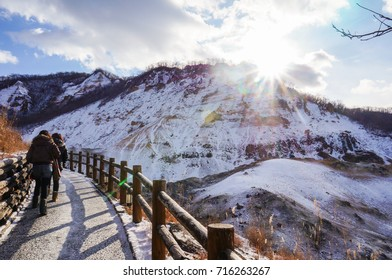 """Traveler walking into Jigokudani, known in English as """"Hell Valley"""" is the source of hot springs for many local Onsen Spas in Noboribetsu, Hokkaido, Japan."""
