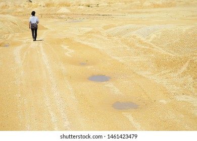 A traveler walking in the middle of a sandy desert