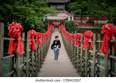 A traveler walks on an ancient suspension bridge in the dujiangyan scenic area of chengdu, China