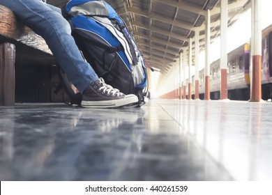 Traveler wearing backpack waiting for a train at trainstation and planing for next trip. Copyspace of travel concept.