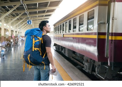 Traveler wearing backpack waitting railway at train station