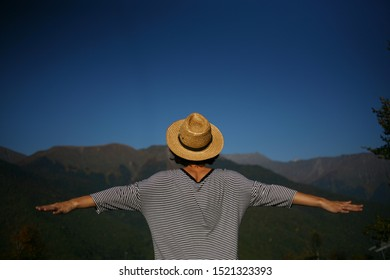 A traveler in a wicker straw hat against the background of mountains and a clear sky stands with his back. outdoor activities. girl looks at the tops of the mountains. man with hands spread wide