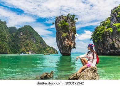 Traveler woman with backpack joy relaxing on sea beach and looking beautiful destination island, James Bond island, Landmark Andaman sea, Travel Thailand, Natural landscape Asia, Summer vacation trip