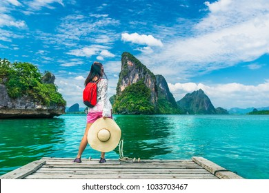 Traveler woman with backpack joy relaxing on floating wood bridge and looking Beautiful destination island, Panyee island, Phang nga bay, Travel Thailand, Natural landscape Asia, Summer vacation trip