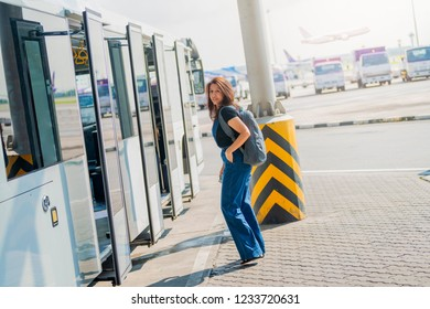 Traveler woman with backpack waiting airport bus and walking transit from airport bus to airplane on runway. Aviation service.