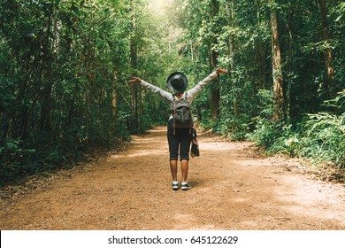 Traveler woman with backpack walking on path in the tropical forest, Krabi, Thailand