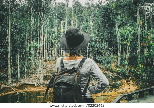 Traveler woman with backpack walking on path in the tropical forest, Krabi, Travel in Thailand