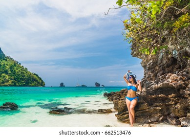 Traveler woman in bikini and big hat relaxing in emerald clear green sea and looking destinations sea beach, Tub island, andaman sea, Krabi province, Thailand