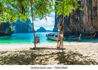 Traveler woman in bikini and big hat relaxing on wooden swing under tree and looking destinations sea beach, Lao Lading island, Andaman sea, Krabi, Travel in Thailand, Summer holiday and vacation trip