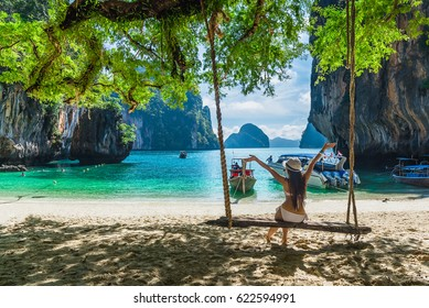 Traveler woman in bikini enjoying relaxing on wooden swing on destinations sea beach her arms open freedom, Lao Lading island, Andaman sea, Krabi, Travel in Thailand, Summer holiday  vacation trip